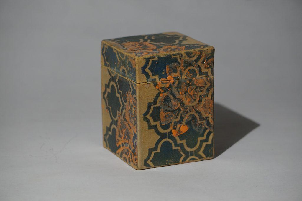 Small lidded box. Orange, black and blue stencil design. Cherry matte interior.